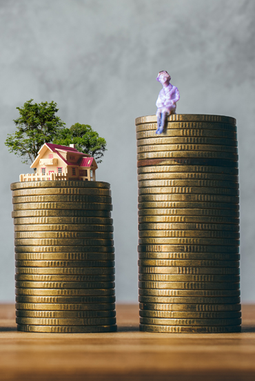 coins stacked up with man and house on top